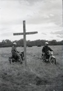 """Young men on their way to Easter Camp stop by a wayside cross erected by their camp mates"".   Later the cross was given a symbolic touch, showing Christ crucified and Christ Risen and Reigning."
